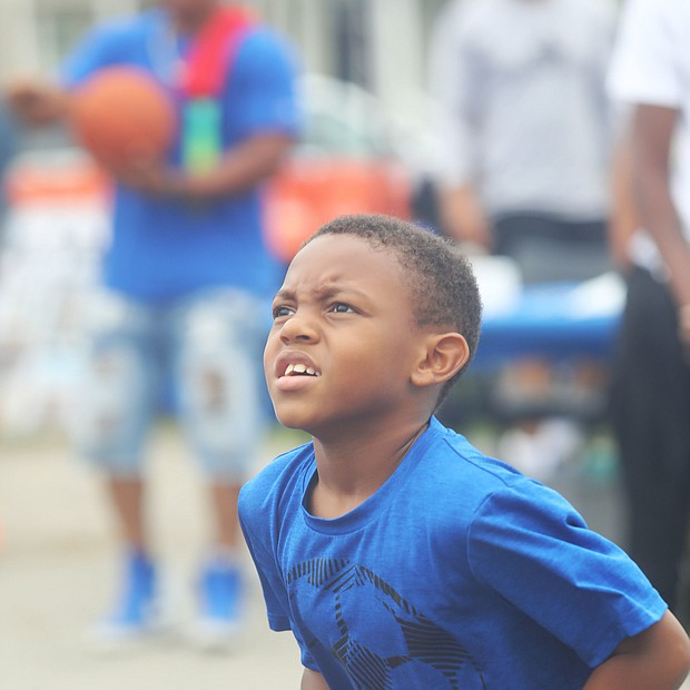 """New court in Church Hill/Dallas Ashford, 8, who has his eye on the hoop as he focuses to take a shot.is on the newly unveiled basketball court behind Mt. Olivet Church at 1223 N. 25th St. in Church Hill.Team Loaded and FeedTheStreetsRVA partnered to bring """"Operation Homebase"""" to the area last Saturday, which included unveiling the court and giving new shoes and T-shirts to youths and providing activities and food at the free community gathering."""