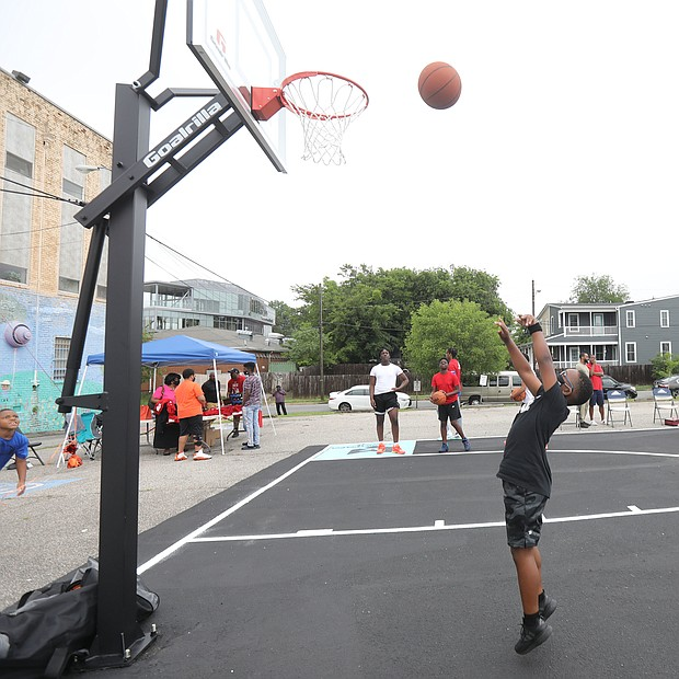 """New court in Church Hill/ Christian Ballard, 9, shows off his skills on the newly unveiled basketball court behind Mt. Olivet Church at 1223 N. 25th St. in Church Hill.Team Loaded and FeedTheStreetsRVA partnered to bring """"Operation Homebase"""" to the area last Saturday, which included unveiling the court and giving new shoes and T-shirts to youths and providing activities and food at the free community gathering."""