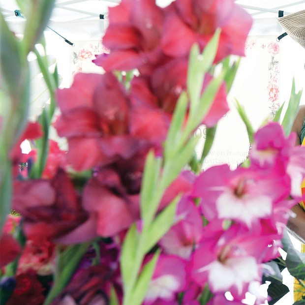 Barbara Payton of Barb's Blooms stands among the festive flowers in her booth at the RVA Black Farmers Market on Saturday at 1700 Blair St. in the city's West End.