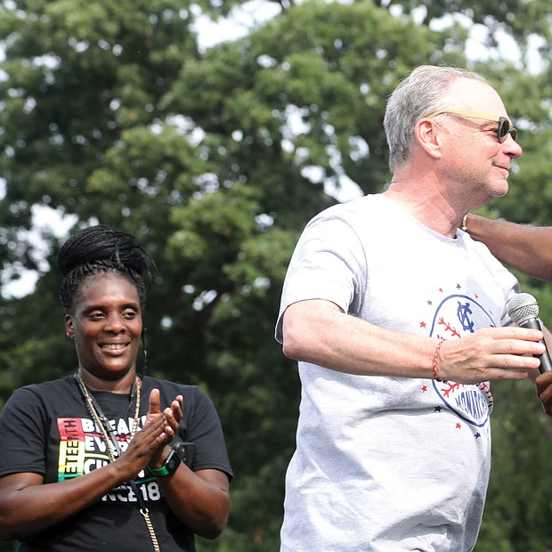 """U.S. Sen. Tim Kaine, left, and Mayor Levar M. Stoney embrace in a show of unity after the senator's remarks and introduction of the mayor during the """"Love and Legacy Juneteenth Jubilee Celebration"""" at the Landing at Fountain Lake in Byrd Park. The event, organized by Sherri Robinson of ShowLove LLC, featured music, dance, entertainment, children's activities and information about community resources."""