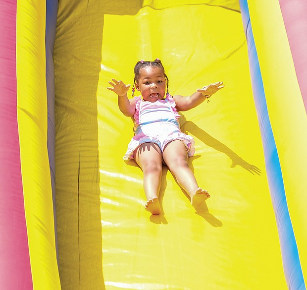 People of all ages enjoyed live music, including the sounds of Plunky Branch, food, games and activities for youngsters, historical interpreters and a car club expo at Juneteenth at Dorey Park in Eastern Henrico County. Four-year-old Milaya Woodly glides down a giant slide.