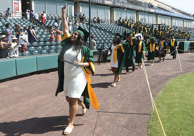 Kym Idella Jeter waves to family and friends in the stands as she walks out with Huguenot High School's new graduates at the end of Monday morning's ceremony at The Diamond on Arthur Ashe Boulevard. Huguenot's was the first of eight Richmond high school commencements over three days at the ballpark.