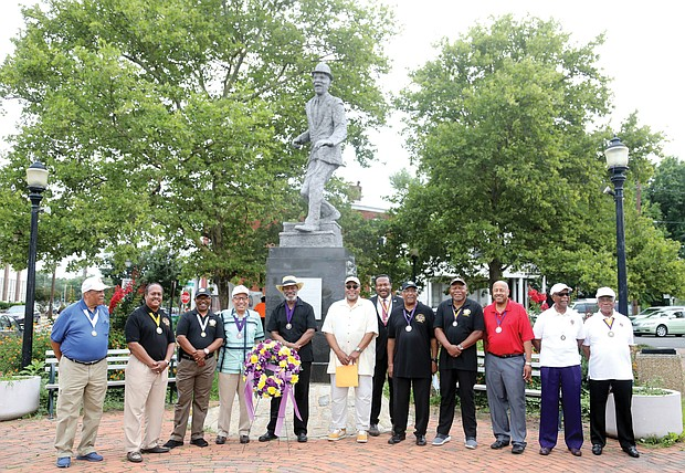 """Members of the Astoria Beneficial Club honor the legacy of Bill """"Bojangles"""" Robinson during its annual commemoration held last Saturday at the statue of Mr. Robinson at Leigh and Adams streets in Jackson Ward. The men's club put the statue in place in 1973 to recognize Mr. Robinson, a Richmond native who rose to international acclaim as a tap dancer and entertainer, because of his impact on his hometown. In 1933, Mr. Robinson purchased a traffic light for $1,400 to be placed at the intersection where his statue now stands after witnessing the danger faced by African-American children trying to cross the busy street. During his lifetime, Mr. Robinson worked for racial equality and civil rights, including more equitable treatment of Black soldiers during World War II and more diverse police departments."""