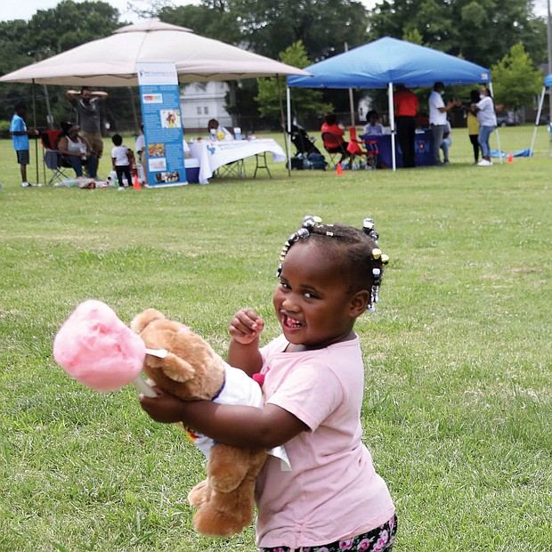 A real sweetie/Amira Jones, 3, has her hands full with a teddy bear and cotton candy at the recent Community Outreach Day at Hotchkiss Field Community Center in North Side. The free event was sponsored by Project Restore, Empowering Youth for Positive Change and the Capital Area Health Network.