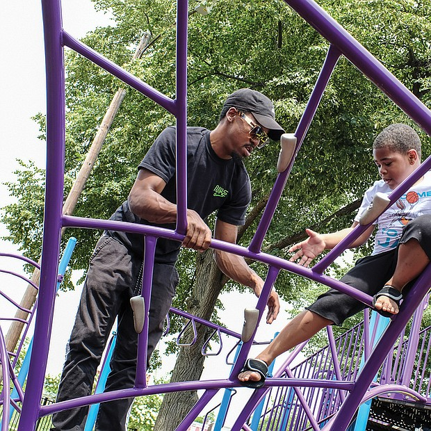 Fun with Dad/Rashe Peoples Jr., 6, takes on the challenge of climbing on playground equipment with the knowledge his dad, Rashe Peoples, has his back. The father and son enjoyed time together last Saturday at Abner Clay Park in Jackson Ward.