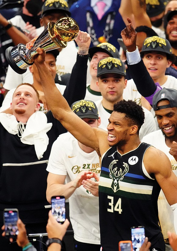 Giannis Antetokounmpo had the Larry O'Brien Trophy in one arm, the NBA Finals MVP trophy in the other and there ...