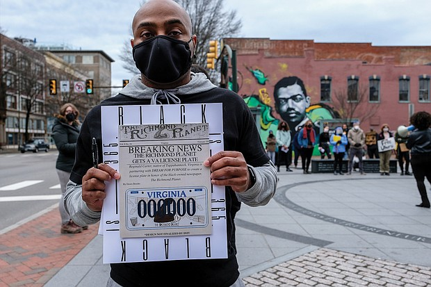 Reginald Carter gathers signatures for his proposed Richmond Planet license plate during a rally earlier this year in Downtown at Adams and Broad streets where a mural of longtime Richmond Planet editor John Mitchell Jr. is located.