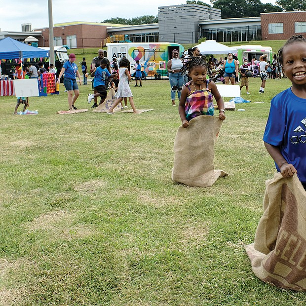 Fun at RPS Summer Fest/Gerald Brown, 5, outdistances his 4-year-old sister, Gabrielle, during a sack race last Saturday at Martin Luther King Jr. Middle School during RPS Summer Fest. The event, sponsored by Richmond Public Schools, provided information for families on how to enroll students for the upcoming school year, while offering music, entertainment, art stations, books and refreshments.