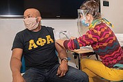 This Alpha Phi Alpha Fraternity member is among the thousands of people who have been vaccinated at various community events by volunteers with the Virginia Commonwealth University Vaccination Corps, which was started in January. Here, Marissa Mackiewicz, a student at the VCU School of Pharmacy and corps member, administers a vaccine at the VCU Health Hub at 25th in