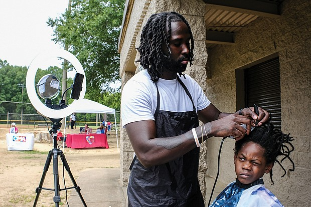 Getting ready for school/The Broad Rock Sports Complex on Old Warwick Road in South Side became a festival of sorts last Saturday as the venue for RPS Summer Fest. The event, sponsored by Richmond Public Schools, featured games, entertainment, food and information on how to enroll students in school this fall along with other community resources. Barber Alonzo Bosher trims the braids of Tyler Sims, 5, as he gets ready for class in September. This was the second Summer Fest hosted by the school system. The first was held July 24 at Martin Luther King Jr. Middle School.