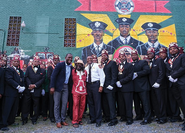 Scores of people turned out Aug. 6 for the official unveiling of the mural honoring the first Black firefighters hired by the City of Richmond. The 10 trailblazers were hired July 1, 1950, and were stationed at Engine Company No. 9 at 5th and Duval streets in Jackson Ward. The commemorative mural was done by local artists Sir James Thornhill, Jason Ford and Kevin Orlosky, and is situated on the side of the Mocha Temple No. 7 Shrine building at 613 N. 2nd St. in Jackson Ward. Members of Mocha Temple pose for a group photo with, at center, Mayor Levar M. Stoney; Mr. Thornhill; and Fire Chief Melvin D. Carter. The unveiling was the kickoff of a weekend of activities sponsored by Engine Company #9 and Associates remembering and honoring the original firefighters.