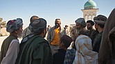 Richard Dickerson, center, meets with local Afghans before a ceremony at Shah Agha Shrine, one of the most holy Islamic sites in the nation, located in the Khakrez District in southern Afghanistan. USAID had worked with U.S. Special Forces and local leaders and villagers to restore the shrine in 2011. Below, Afghan workers at Kandahar Airfield pause to participate in an Eid ceremony at the airfield in 2011.