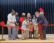 Celebrating Cardinal Elementary's dedication with a ribbon-cutting are, several students and, from left, School Board member Nicole Jones; Principal Juvenal E. Abrego- Meneses; School Board Chairwoman Cheryl L. Burke; Delegate Betsy B. Carr; Superintendent Jason Kamras and the Cardinal mascot.