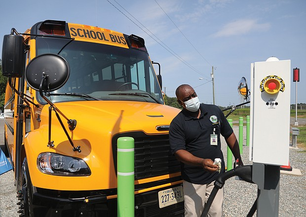 """New wheels for Chesterfield schools/Al Parham, supervisor of Chesterfield County Public Schools' bus fleet, wipes off the plug-in station for the school system's two new electric school buses during a """"Plug-in Ceremony"""" Aug. 12 at the county's bus maintenance facility, 7300 Walmsley Blvd. School and county officials, along with officials from Dominion Energy, attended the event held to show off the two new vehicles that were delivered in May. Chesterfield is the first municipality in Metro Richmond to receive the electric school buses through a program sponsored by Dominion Energy. Under the program, school districts pay no more for the electric buses than they would for a diesel model. The program also covers the cost of the charging stations. The first 50 buses were provided under the program in 2020 to 14 school districts in various parts of the state. (photo: Regina H. Boone/Richmond Free Press)"""