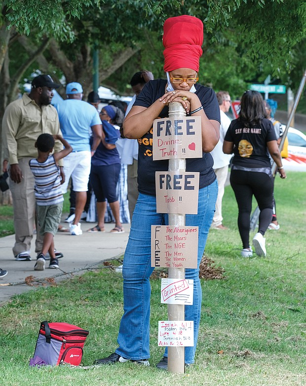 Kimberly Dyke-Harsley displays her own message about freedom as she listens to the speakers at last Saturday's parole restoration rally at Chimborazo Park.