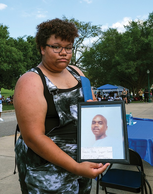 Savannah Watkins, 19, holds a picture of her father, Calvin Watkins, who has been incarcerated since 2004 at Buckingham Correctional Center. She said she doesn't remember her father outside of prison.