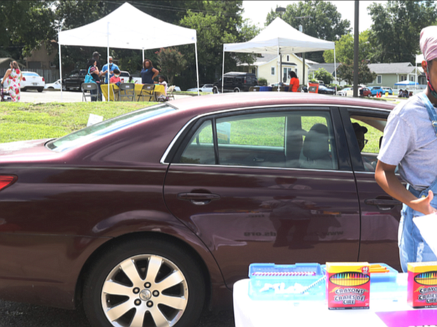"""Karma Delvalle, 13, picks up school supplies last Saturday during the 15th Annual """"We Care"""" festival at Overby-Sheppard Elementary School in Highland Park. Because of the pandemic, the festival was set up as a drive-thru event in the school's driveway, with cars inching along past the booths and people getting out to pick up materials. Festival-goers enjoyed music and picking up the giveaways from various community organizations. COVID-19 testing and vaccines were available at the festival from Capital Area Health Network."""