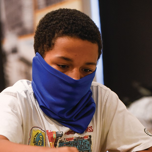 Making a move/Denzel Johnson, 14, a student at CodeRVA Regional High School, makes a bold move during the Bright Minds RVA Chess Tournament last Friday at the Black History Museum and Cultural Center of Virginia. The pilot program drew area youngsters to classes and competition sponsored by the Bernice E. Travers Foundation. (photo by Clement Britt)