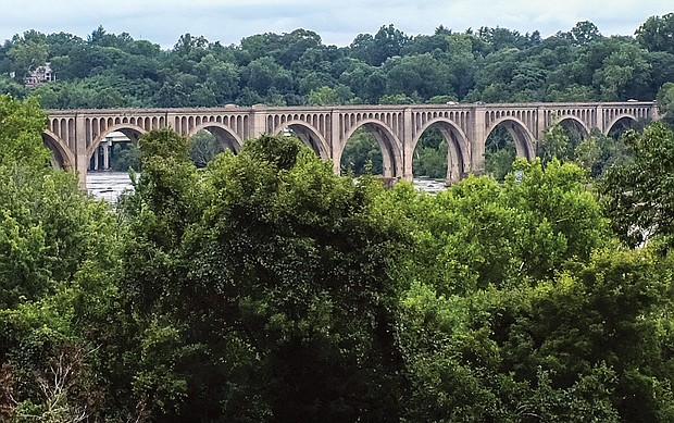 """Cityscape:Slices of life and scenes in Richmond/This elegant Richmond railroad bridge over the James River has stood the test of time. Woodrow Wilson was still president, the prohibition of liquor begins and the raging pandemic """"Spanish flu"""" was killing millions of people when the Richmond, Fredericksburg & Potomac and CSX-predecessor Atlantic Coastline railroads built the structure in 1919. Location: Between the Boulevard and Powhite Parkway bridges. Legendary engineer John E. Greiner designed the iconic arched bridge that was among the first rail bridges to be made of poured concrete. Dubbed the """"million-dollar bridge,"""" the double-track bridge allowed trains to move through Richmond more quickly and to cross east-west rail lines that ran along both sides of the river. Considered an engineering marvel, the bridge continues to draw admirers."""