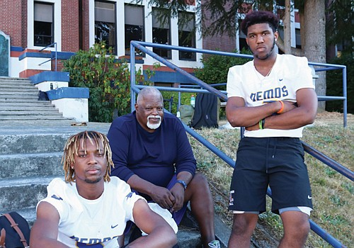 Long-time winning football coach and youth leader Anthony Stoudamire (center) is back as coach of the Jefferson High School football team, flanked by two of the team's pivotal players awaiting Friday's home opener, Demos quarterback Dondrae Fair (left) and senior defensive safety Trejon Williams.