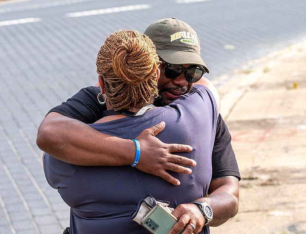 Devon Henry, president and chief executive officer of the Newport News-based Team Henry Enterprises, hugs his mother, Freda Thornton, after the Lee statue came down on Wednesday. Mr. Henry's company was responsible for the removal and disassembly of the statue for storage in an undisclosed secure location. He faced death threats after his company's role in removing Richmond's other Confederate statues in July 2020 was made public.
