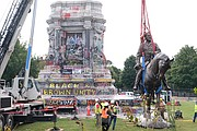 Workers carefully lower to the ground Wednesday the 12-ton bronze statue of Confederate Gen. Robert E. Lee from the large stone pedestal on Monument Avenue where it has stood since 1890.