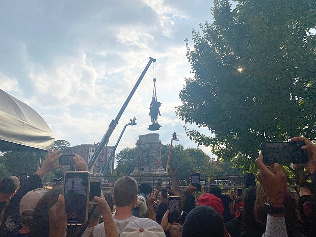 Onlookers cheer and take pictures as the Lee statue is lowered to the ground and dismantled by workers on Wednesday before being transported to a warehouse. The state will decide what to do with the statue and its large stone pedestal.