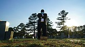 """Mortician Shawn Troy stands at the grave of his father, William Penn Troy Sr., at Hillcrest Cemetery outside Mullins, S.C., on Sunday, May 23, 2021. The elder Troy, who developed the cemetery, died of COVID-19 in August 2020, one of many Black funeral directors to succumb to the pandemic. """"I don't think I'll ever get over it,"""" he said. """"But I'll get through it."""""""