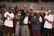 Former Panthers football Coach Willard Bailey waves to the crowd during a halftime ceremony where he was honored at the Willard Bailey Classic. At different times, Coach Bailey led the football programs at both VUU and its opponent last Saturday, Virginia University of Lynchburg. At right is Joe Taylor, VUU's vice president of intercollegiate athletics and community wellness.