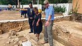 Dr. Reginald F. Davis, left, pastor of First Baptist Church in Williamsburg, Connie Matthews Harshaw, a member of First Baptist, and Jack Gary, Colonial Williamsburg's director of archaeology, stand Oct 6 at the brick-and-mortar foundation of the old church unearthed in Williamsburg's historic area.