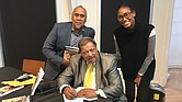 """Former Richmond City Councilman Henry W. """"Chuck"""" Richardson signs copies of his new memoir, """"Cease Fire! Cease Fire!"""", last Saturday for John H. Mitchell, the great-great-nephew of the late Richmond Planet newspaper editor John Mitchell Jr., and Liza Mickens, the great-great-granddaughter of the late noted businesswoman Maggie L. Walker. Location: Black History Museum & Cultural Center of Virginia in Jackson Ward."""