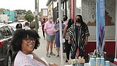 """Queen of ice cream Rabia Kamara gives out samples of her winning Ben & Jerry's ice cream creation """"Bia's Black Joy Sundae"""" last week to people lined up outside her shop, Ruby Scoops Ice Cream & Sweets, on Brookland Park Boulevard."""